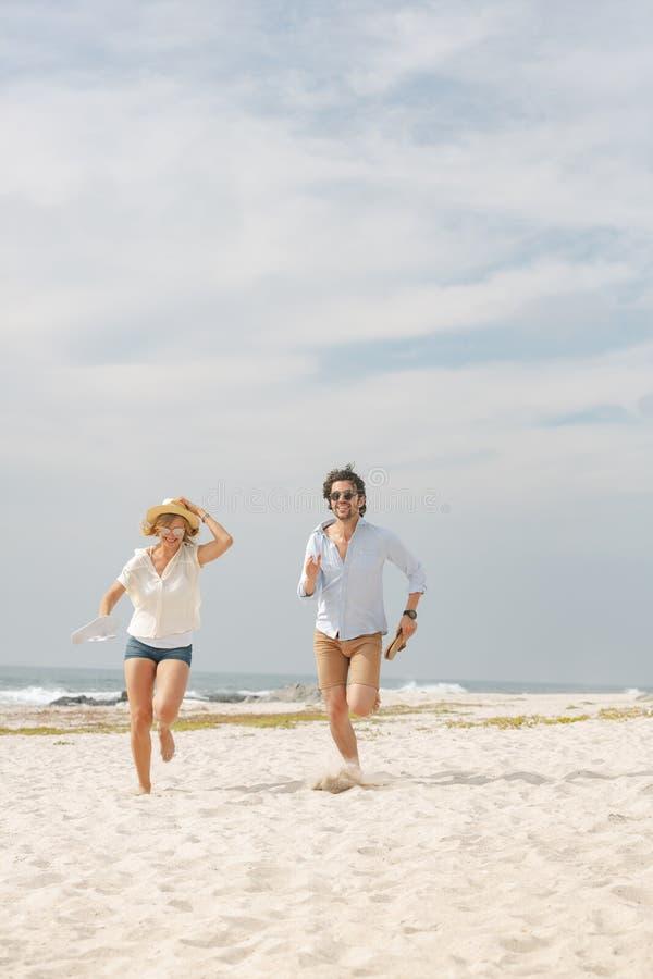 Lyckliga Caucasian par som kör på stranden på solig dag royaltyfria bilder