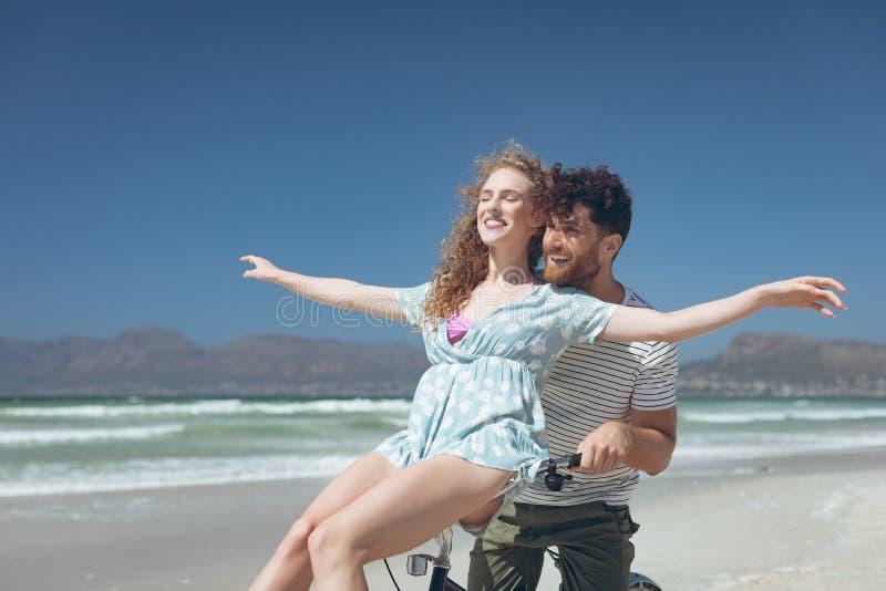 Lyckliga Caucasian par som tycker om på cykeln på stranden royaltyfria foton