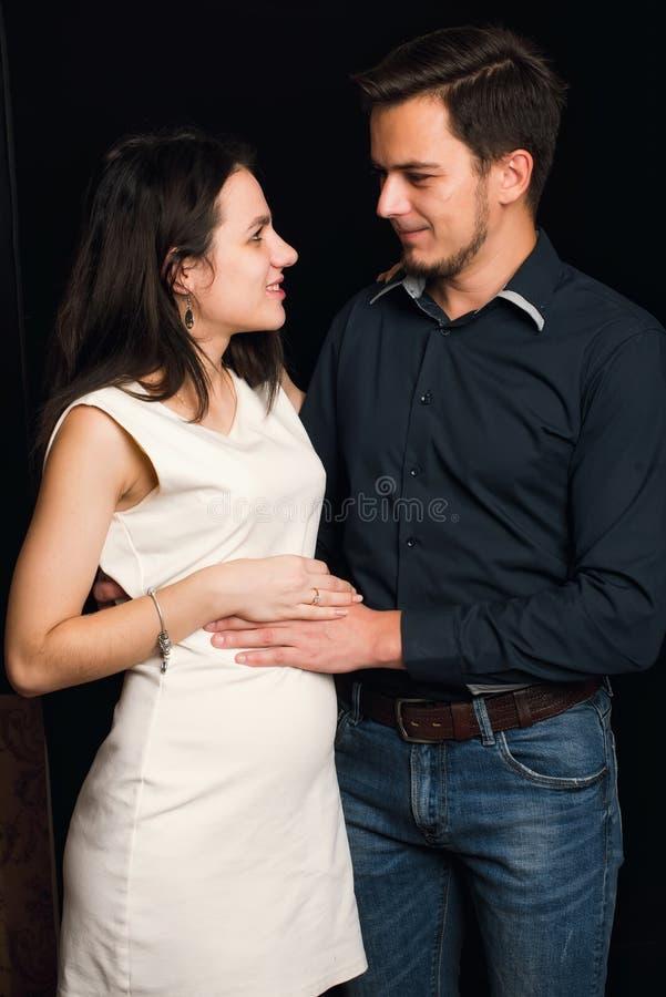 Lyckliga Caucasian par som väntar på födelsen av ett barn Mannen kramar en gravid flicka fotografering för bildbyråer