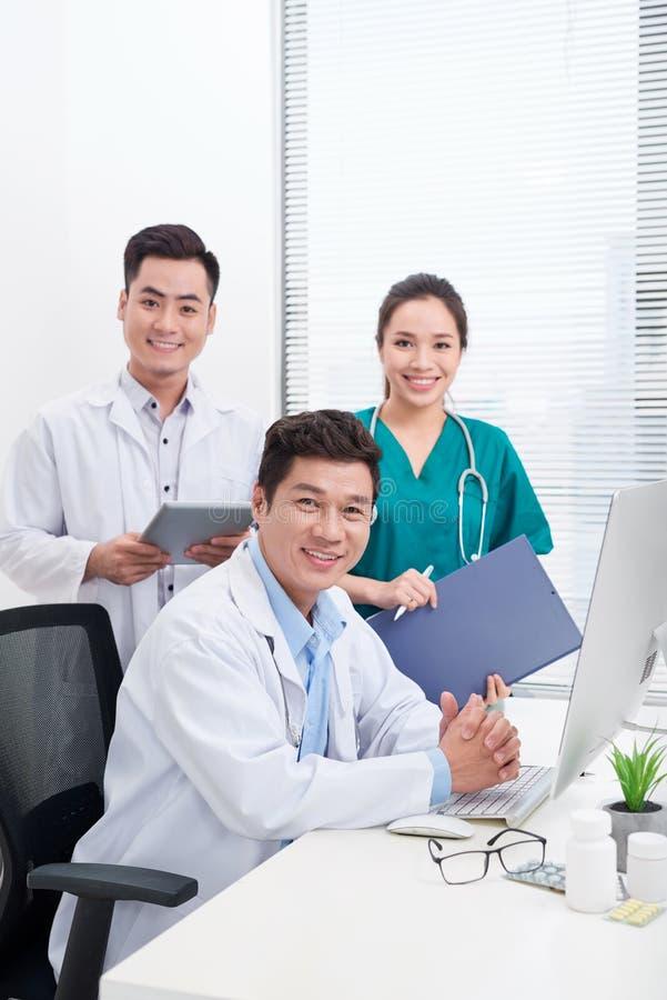 Lyckliga doktorer på sjukhuskontoret vart begreppshanden har den sena pillen f?r sjukv?rdhj?lp royaltyfria foton
