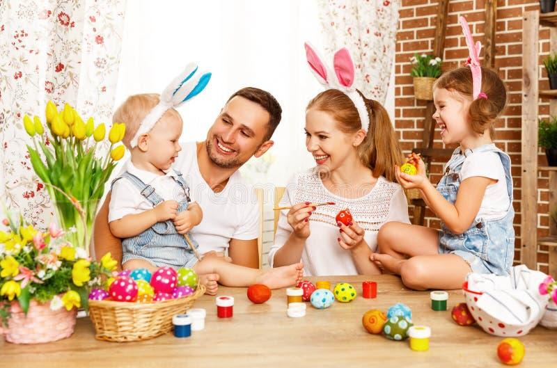 Lyckliga easter! den familjmodern, fadern och barn målar ägg för royaltyfri foto