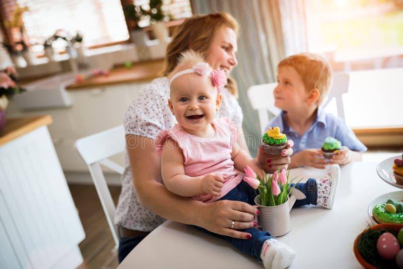 lyckliga easter En moder och henne ungar som målar påskägg arkivfoto