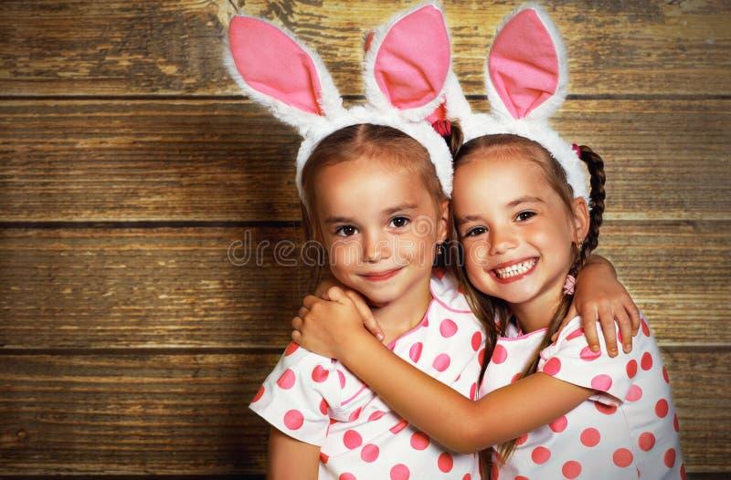 Lyckliga easter! gulligt kopplar samman flickasystrar som kläs som kaniner på wo royaltyfri fotografi