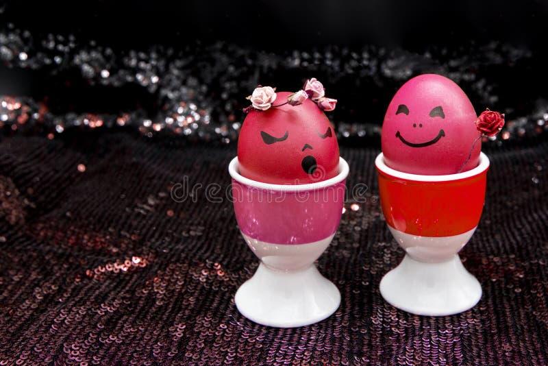 Lyckliga easter röda ägg med den målade utdragna tecknade filmen vänder mot på svart skinande bakgrund Pojken ger flickarosblomma royaltyfri bild
