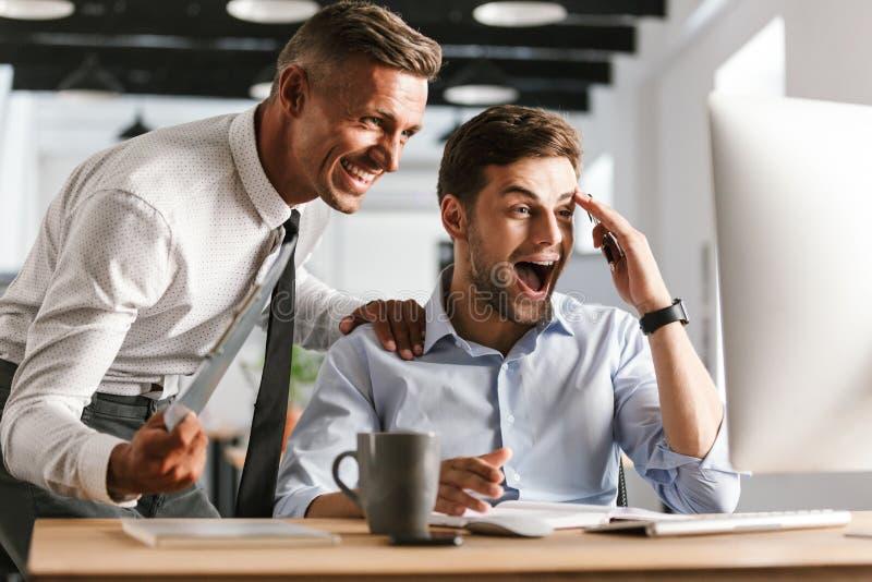 Lyckliga emotionella mankollegor i regeringsställning som arbetar med datoren royaltyfria bilder