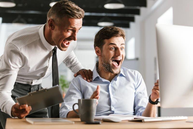 Lyckliga emotionella mankollegor i regeringsställning som arbetar med datoren royaltyfria foton