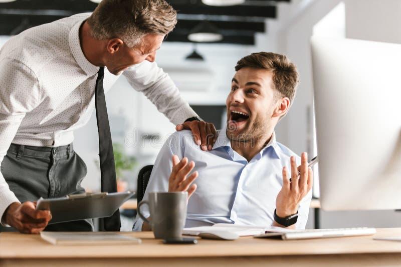 Lyckliga emotionella mankollegor i regeringsställning som arbetar med datoren arkivfoto