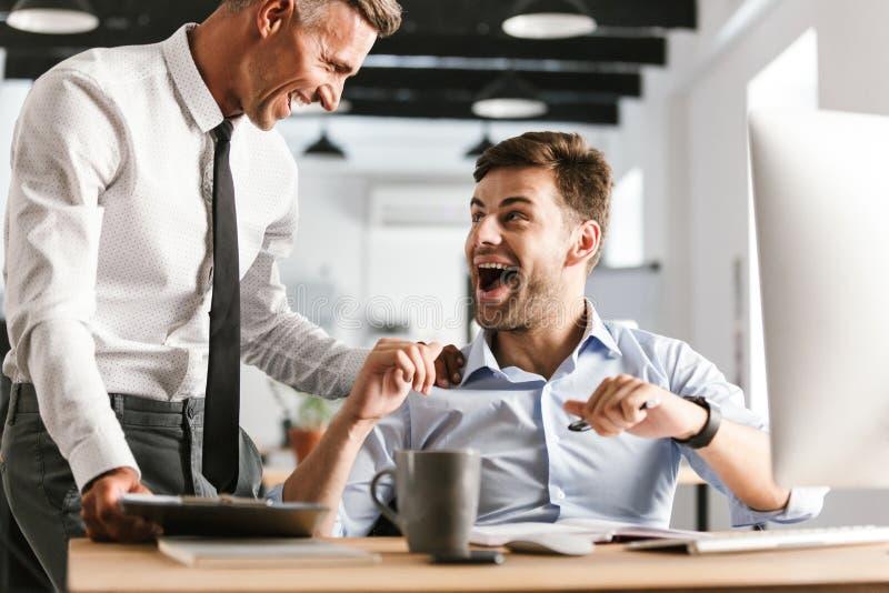 Lyckliga emotionella mankollegor i regeringsställning som arbetar med datoren royaltyfri foto