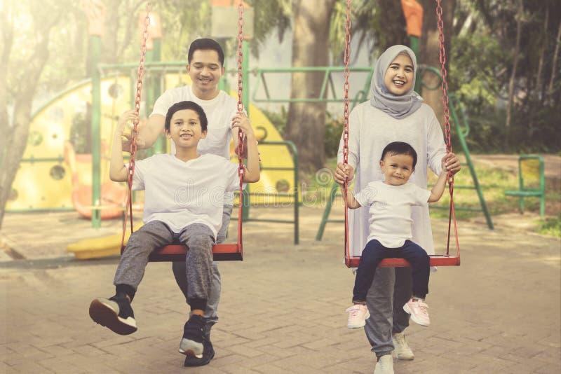 lyckliga föräldrar för barn skjuta deras swing arkivfoton