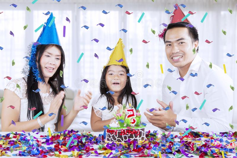 Lyckliga föräldrar firar födelsedag av deras dotter arkivfoton