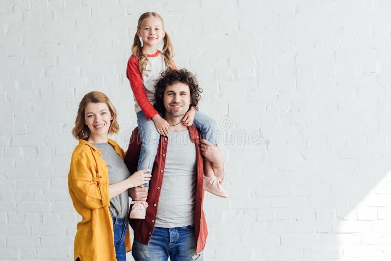 lyckliga föräldrar med den förtjusande lilla dottern som ler på kameran royaltyfria foton