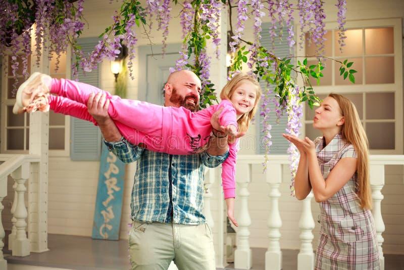 Lyckliga föräldrar med dottern har gyckel som spelar rymma barnet på hans händer, i hem för borggårdsommarfamilj arkivbild