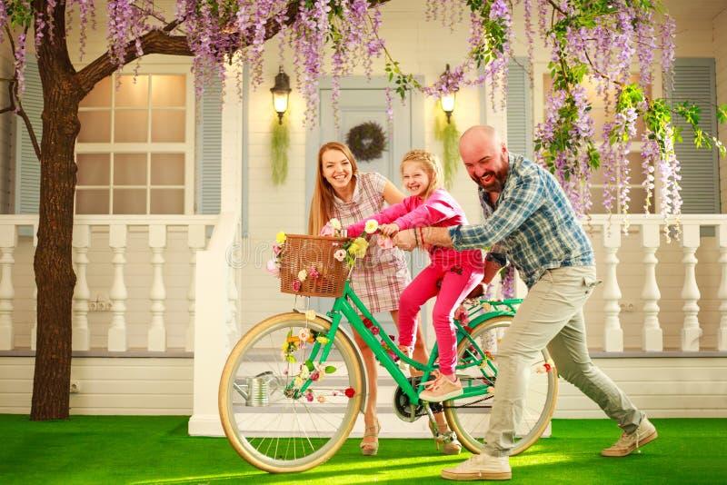 Lyckliga föräldrar med ett barn, dotter, lär att rida en cykel, semestrar för familjlivsstilsommar hemma arkivbild