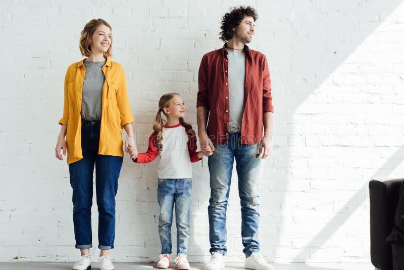 lyckliga föräldrar med gulliga små dotterinnehavhänder, medan stå tillsammans royaltyfria bilder