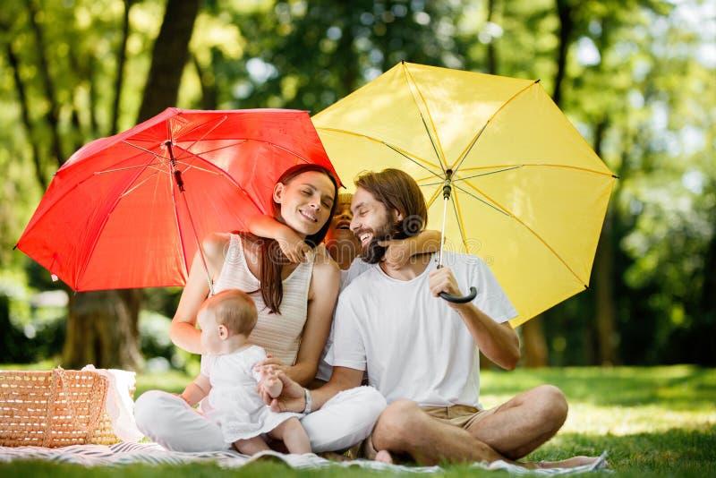Lyckliga föräldrar med två ungar har att vila på gräsmattan under de ljusa röda och gula paraplyerna som täcker dem från solen royaltyfria bilder