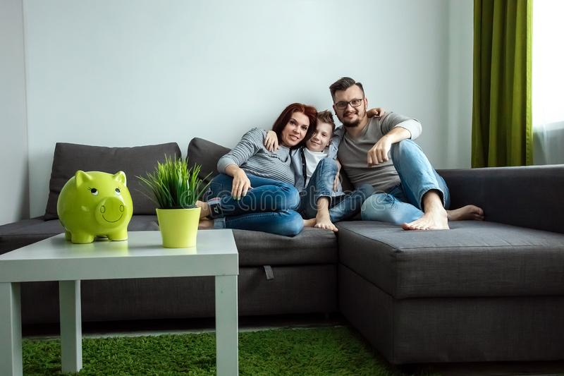 Lyckliga föräldrar och son som har gyckel som killar att sitta tillsammans på soffan, gladlynt skratta för par som spelar en lek  royaltyfria foton