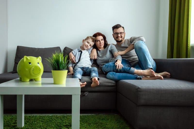 Lyckliga föräldrar och son som har gyckel som killar att sitta tillsammans på soffan, gladlynt skratta för par som spelar en lek  royaltyfria bilder