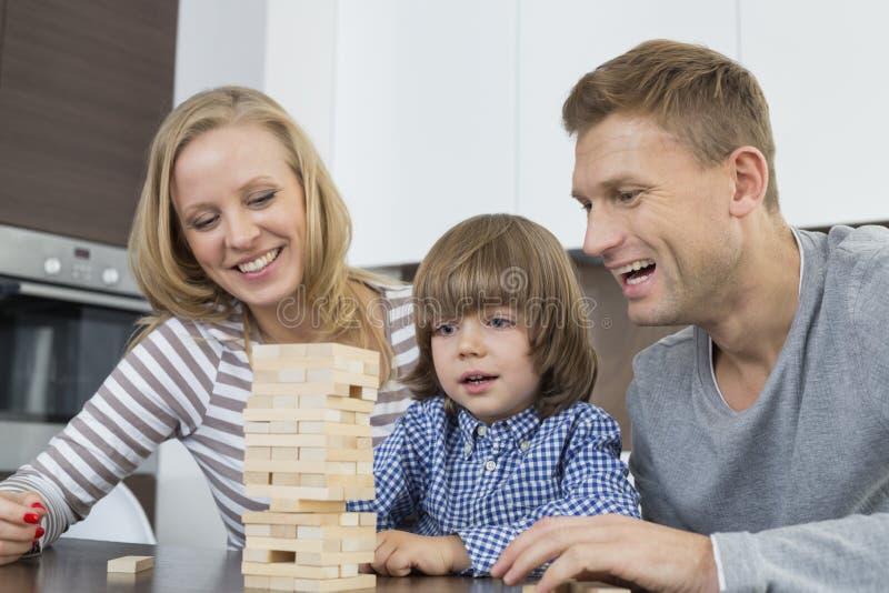 Lyckliga föräldrar och son som spelar med hemmastadda träkvarter royaltyfria bilder
