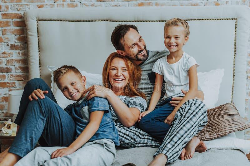 Lyckliga föräldrar och två ungar som tillsammans kopplar av royaltyfri fotografi