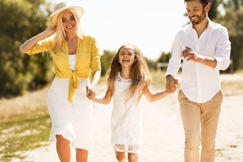 Lyckliga föräldrar som går med dottern som rymmer händer royaltyfria bilder