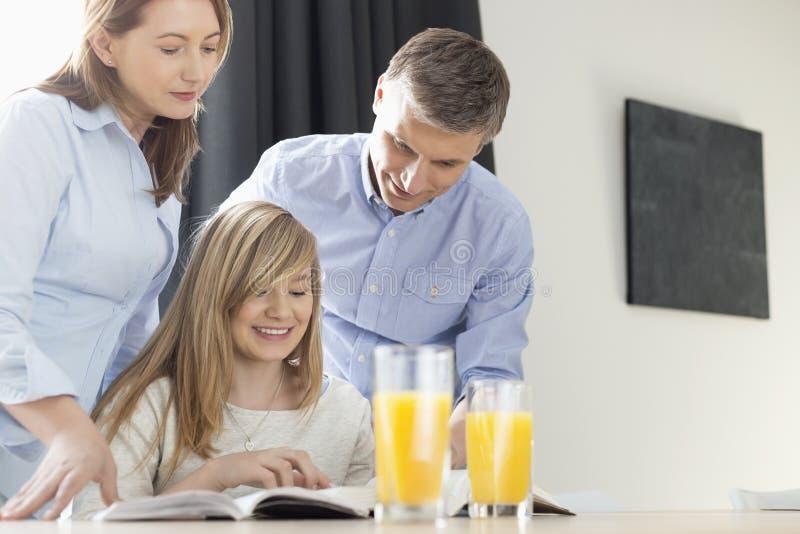 Lyckliga föräldrar som hemma hjälper dottern i läxa arkivfoto