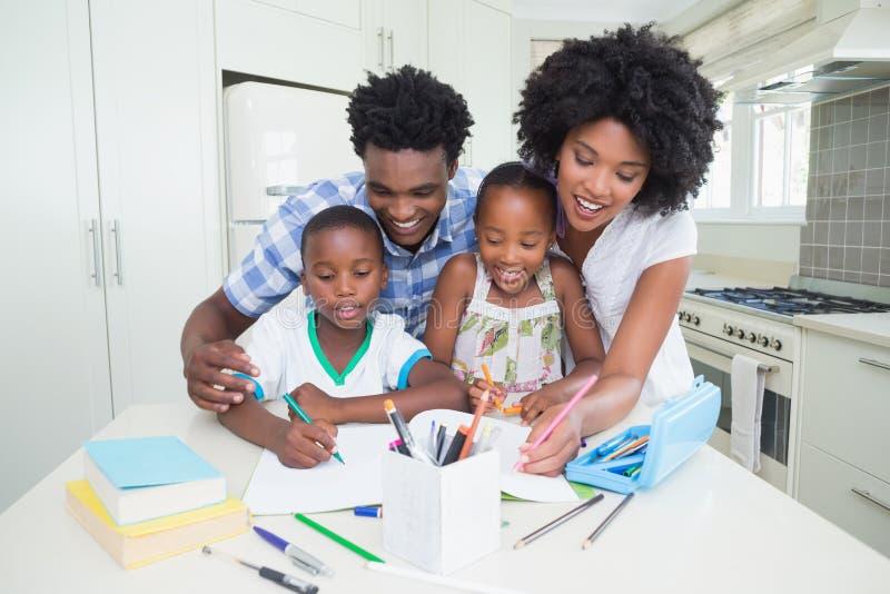 Lyckliga föräldrar som hjälper barn med läxa arkivfoto