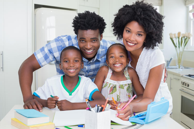 Lyckliga föräldrar som hjälper barn med läxa royaltyfri bild
