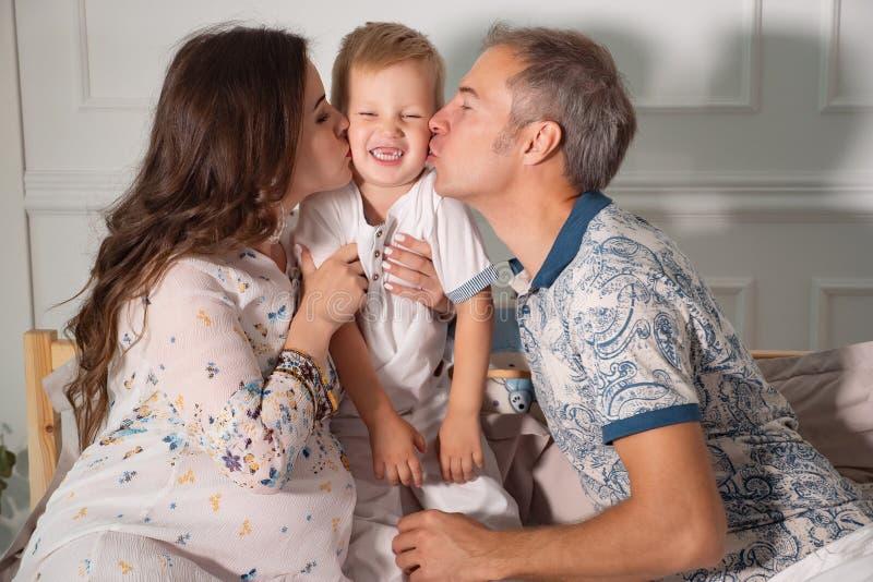 Lyckliga föräldrar som kysser pysen i säng arkivfoto