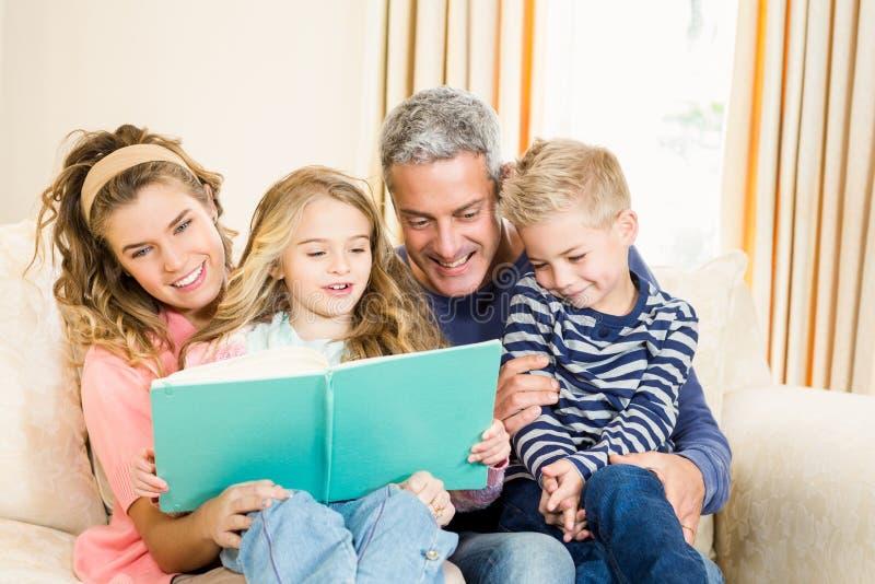Lyckliga föräldrar som läser till deras ungar fotografering för bildbyråer