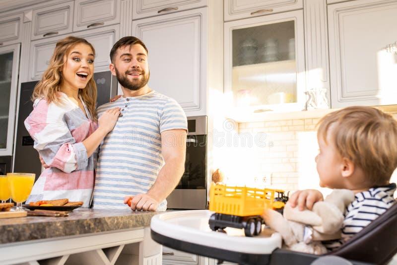 Lyckliga föräldrar som ser, behandla som ett barn arkivfoton