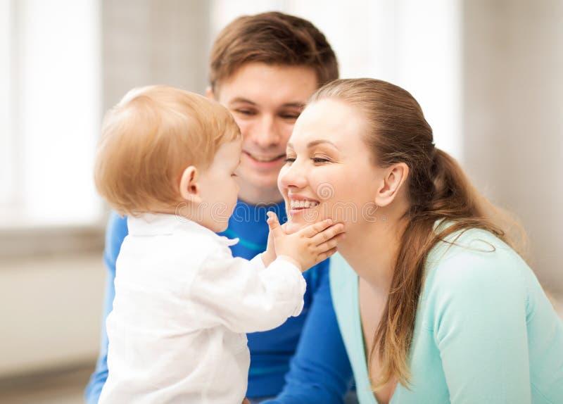 Lyckliga föräldrar som spelar med förtjusande, behandla som ett barn royaltyfri foto