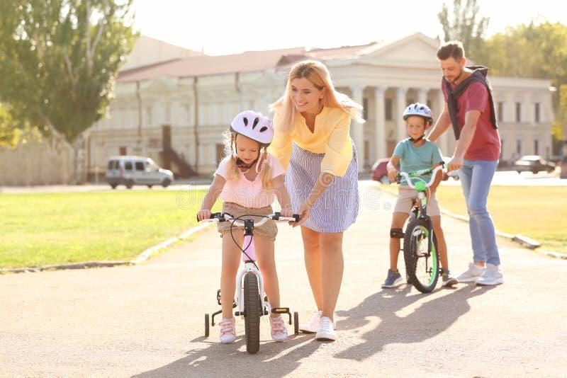 Lyckliga föräldrar som undervisar barn att rida cyklar royaltyfria bilder