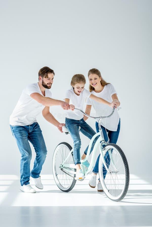Lyckliga föräldrar som undervisar gullig liten dotterridning, cyklar royaltyfri foto