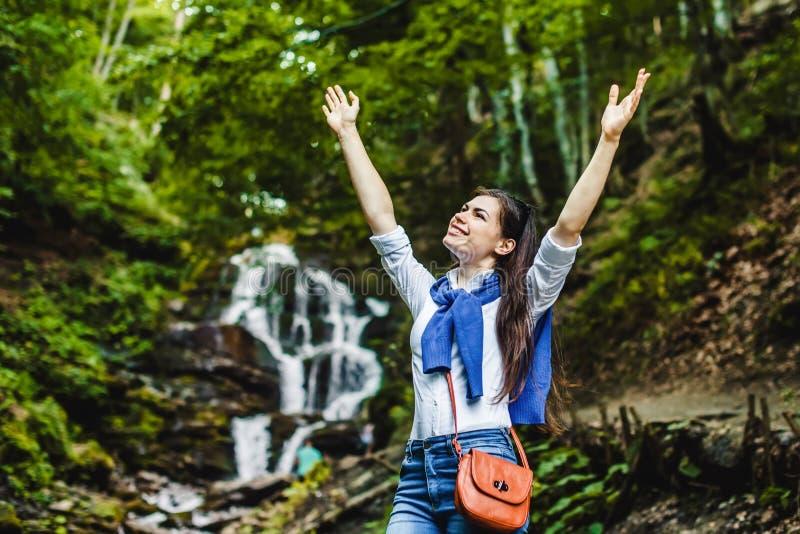 Lyckliga fördelande händer för ung kvinna som tycker om naturen med vattenfallet i bakgrund royaltyfri foto