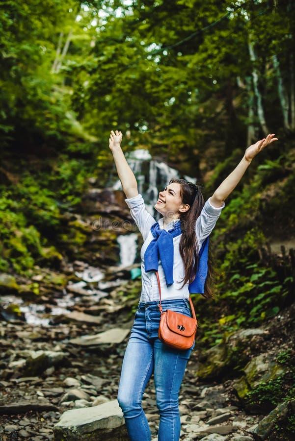 Lyckliga fördelande händer för ung kvinna som tycker om naturen med vattenfallet i bakgrund royaltyfria bilder