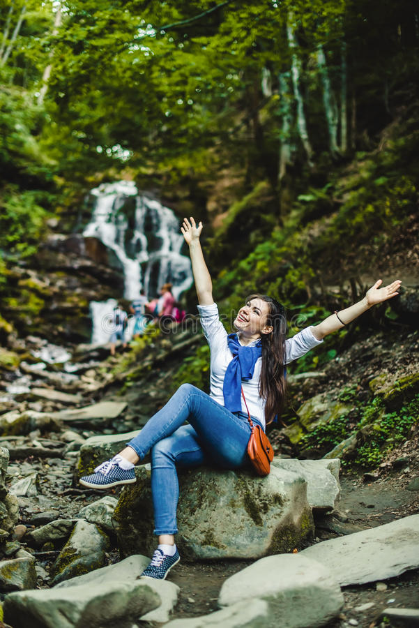 Lyckliga fördelande händer för ung kvinna som tycker om naturen med vattenfallet i bakgrund arkivfoton