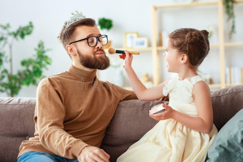 Lyckliga faders dag! barndottern i krona g?r makeup till pappan royaltyfri bild