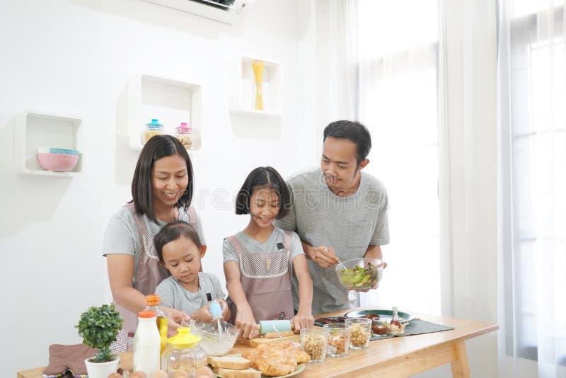Lyckliga familjasiatkockar i köket fotografering för bildbyråer