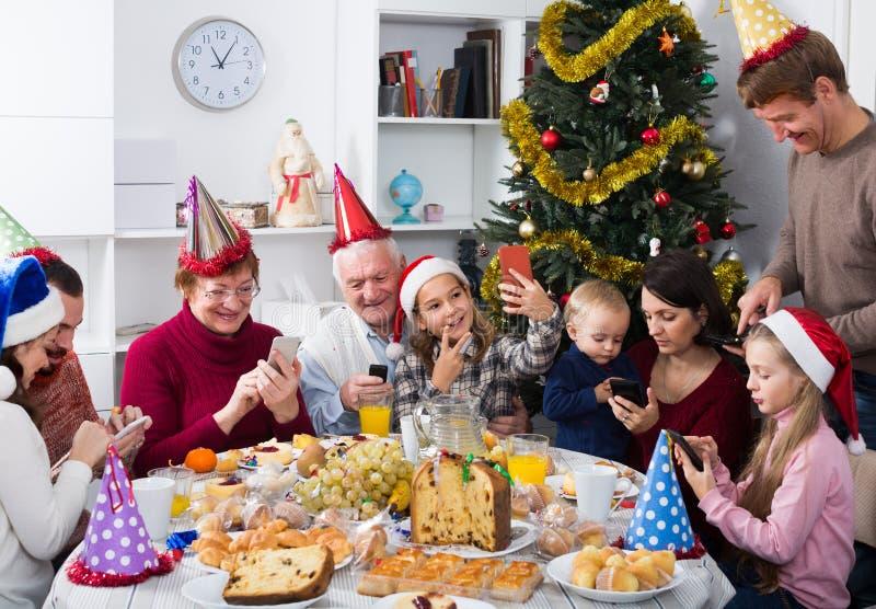 Lyckliga familjemedlemmar som ser till och med foto royaltyfria foton