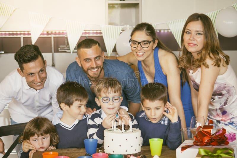 Lyckliga familjer med barn som firar runt om en kaka för en födelsedag fotografering för bildbyråer