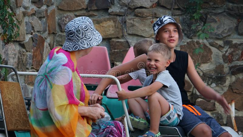Lyckliga familjer med tre pojkar i borggård royaltyfri fotografi