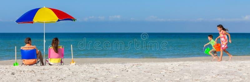 Lyckliga familjföräldrar och barn som har gyckel i solstolar på en strand arkivbild