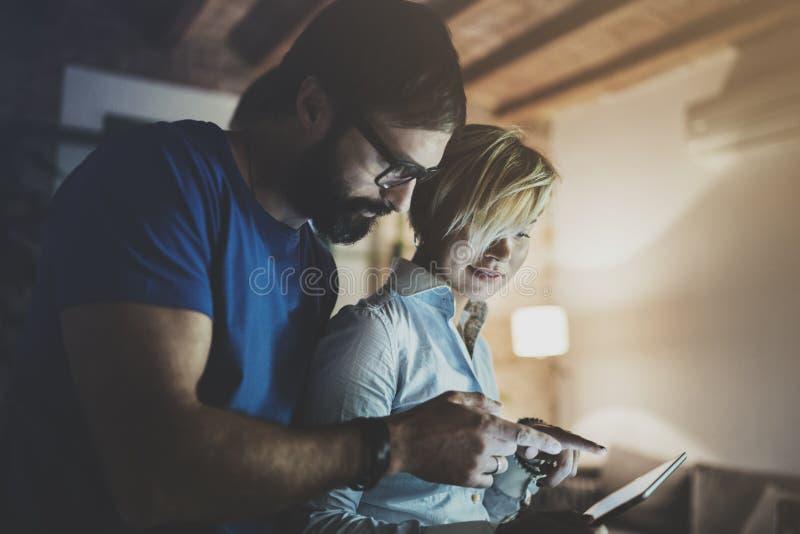 Lyckliga familjpar genom att använda den elektroniska minnestavlan i livingroom hemma Skäggig man i ögonexponeringsglas som gör k arkivfoto