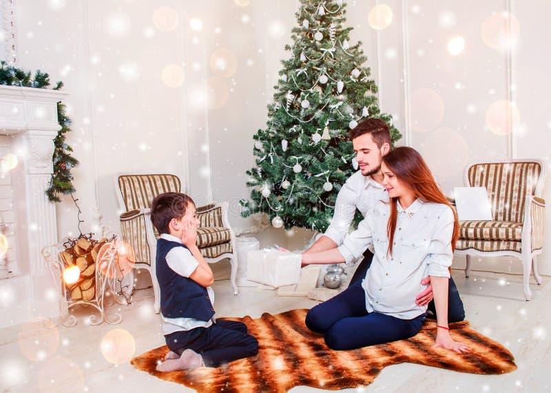 Lyckliga familjpar ger gåvor i vardagsrummet, bak den dekorerade julgranen, ljuset för att ge en hemtrevlig atmosfär royaltyfria bilder