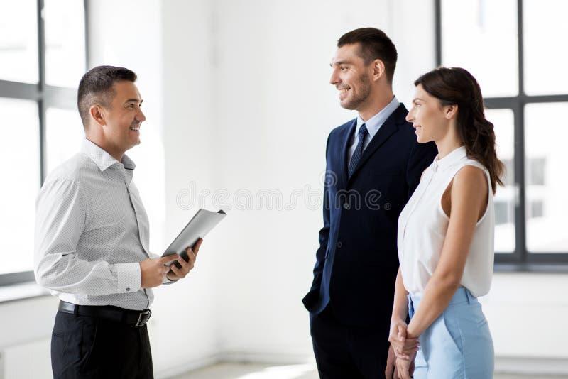 Lyckliga fastighetsmäklaremötekunder på det nya kontoret royaltyfri foto