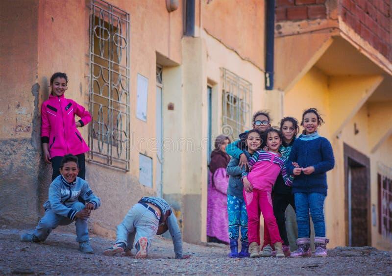 Lyckliga fattiga vänliga barn flicka och pojke i den Marocko byn med det gamla huset royaltyfri foto