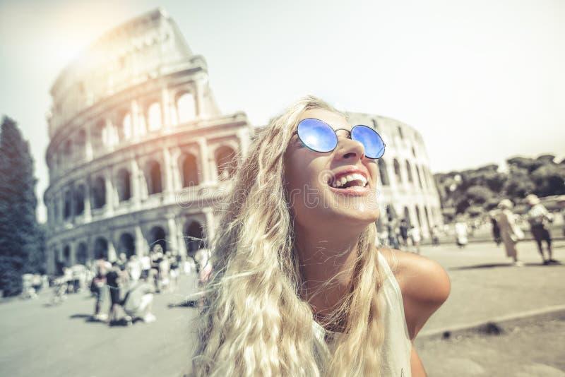 Lyckliga ferier i Rome som framme ler ungt blont av colosseumen i Rome i Italien arkivfoton