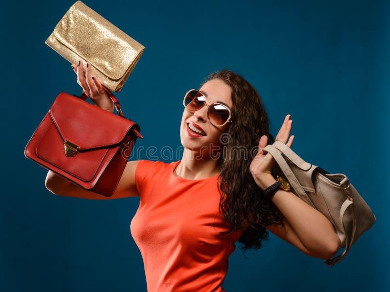 Lyckliga flickahållpåsar Röd klänning Kvinnlig härlig modell royaltyfri bild