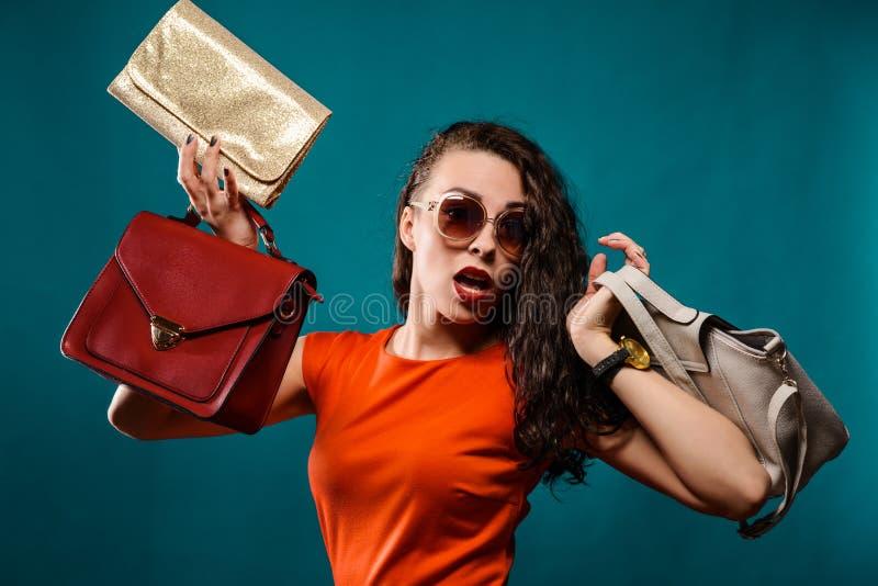 Lyckliga flickahållpåsar Röd klänning Kvinnlig härlig modell arkivfoton