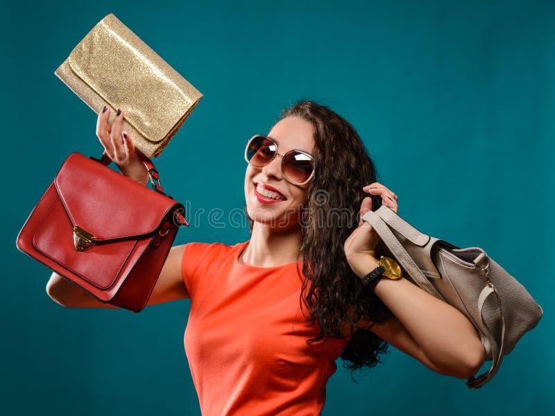 Lyckliga flickahållpåsar Röd klänning Kvinnlig härlig modell royaltyfria foton